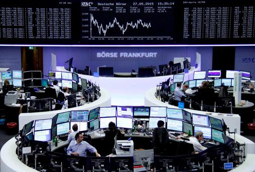 Traders are pictured at their desks in front of the DAX board at the Frankfurt stock exchange. Photo: Reuters