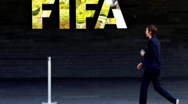 A member of staff walks past the logo of soccer's international governing body FIFA at their headquarters in Zurich. Photo: Reuters