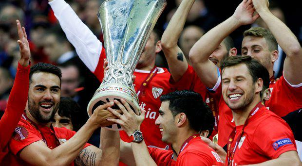 Sevilla players hold the trophy after Sevilla won 3-2 during the final of the soccer Europa League between FC Dnipro Dnipropetrovsk and Sevilla FC at the National Stadium in Warsaw, Poland, Wednesday, May 27, 2015. (AP Photo/Czarek Sokolowski)