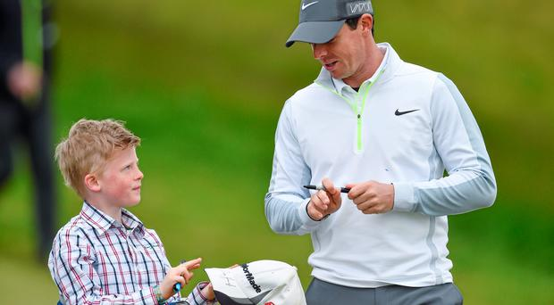 27 May 2015; Rory McIlroy signs an autograph for a young fan during his round. Dubai Duty Free Irish Open Golf Championship 2015, Pro-Am. Royal County Down Golf Club, Co. Down. Picture credit: Ramsey Cardy / SPORTSFILE