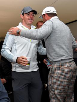 NEWCASTLE, NORTHERN IRELAND - MAY 27: Graeme McDowell of Northern Ireland greets Rory McIlroy of Northern Ireland as he leaves a press conference during the Pro-Am round prior to the Irish Open at Royal County Down Golf Club on May 27, 2015 in Newcastle, Northern Ireland. (Photo by Ross Kinnaird/Getty Images)
