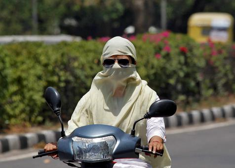 A woman rides a motorcycle with her face covered to protect herself from sun stroke on a hot summer day in Chandigarh, India, May 28, 2015. REUTERS/Ajay Verma