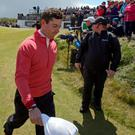 Rory McIlroy reacts as he leaves the 9th green