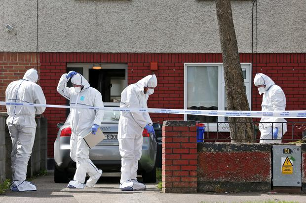 Members of the Garda Crime Scene Investigation Unit examine the scene of the shooting of Alan O'Neill at a house on the Kiltalown Road in Tallaght.