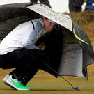 Northern Irish golfer Rory McIlroy shelters from rain and wind on the 6th tee on the second day of the Irish Open at the Royal County Down Golf Club