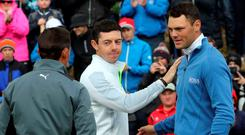Northern Irish golfer Rory McIlroy (C) shakes hands with US golfer Rickie Fowler (L) and Germany's Martin Kaymer (R) after finishing on the 18th green on the second day of the Irish Open at the Royal County Down Golf Club in Newcastle in Northern Ireland on May 29, 2015. AFP PHOTO / PAUL FAITHPAUL FAITH/AFP/Getty Images
