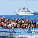 Hundreds of migrants in an overcrowded wooden-hulled boat in the Mediterranean Sea just north of the coast of Libya