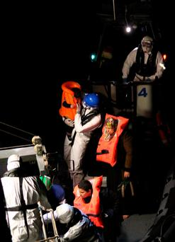 A member of the Irish Naval Service helps to rescue a mother and her baby off the coast of Libya on Thursday night