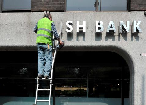 Workers remove the signage outside Anglo Irish Bank's HQ