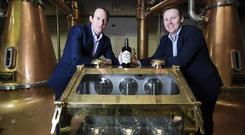 Pictured (l-r) are brothers Stephen and Jack Teeling and the brass spirit safe that holds the first whiskey spirit to be produced in Dublin in almost four decades