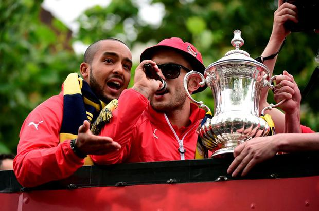 Arsenal's Jack Wilshere and Theo Walcott hold the FA Cup trophy as they stand on the top deck of an open-topped bus during the Arsenal victory parade in London