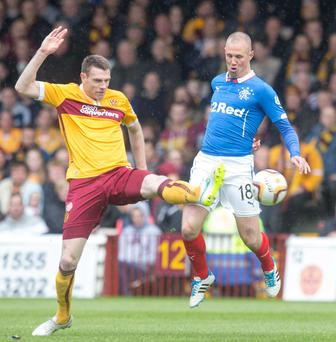 Rangers' Kenny Miller challenges Stephen McManus of Motherwell for control of the ball
