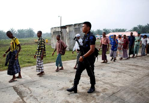 An Indonesian police officer walks beside Rohingya migrants who arrived in Indonesia last week Credit: Darren Whiteside