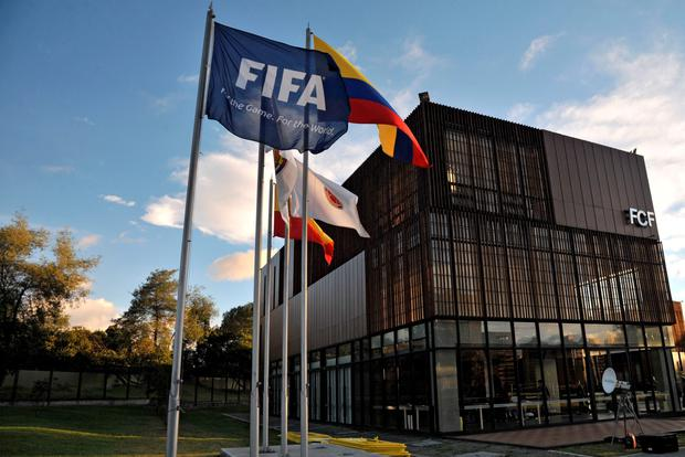 The FIFA's flag and the Colombian national flag flutter at the entrance of Colombia's Football Federation (FCF) headquarters prior to FCF's president Luis Bedoya's press conference in Bogota on June 1, 2015, following last week's arrest of FIFA officials over corruption charges filed by US authorities