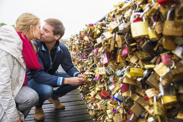 A couple lock a padlock to a bridge in Paris, France