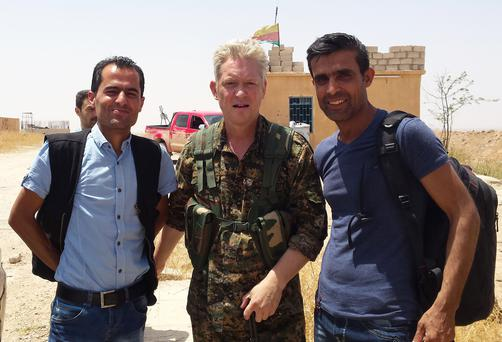 In this handout photo provided by Kurdish journalist Mohammed Hassan, taken on May 19, 2015, Michael Enright, center, a British actor who has had minor roles in Hollywood films, wears the Kurdish fighters military uniform after he joined them battling against the Islamic State group, near Tel Tamr town, northeast Syria. (Mohammed Hassan via AP )