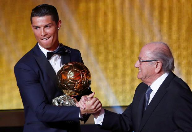Real Madrid's Cristiano Ronaldo of Portugal, is congratulated by FIFA President Sepp Blatter (R) after winning the FIFA Ballon d'Or 2014