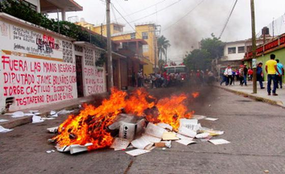 A pile of burning electoral material is seen outside the office of the National Electoral Institute in the state of Oaxaca, Mexico Credit: REUTERS/Stringer