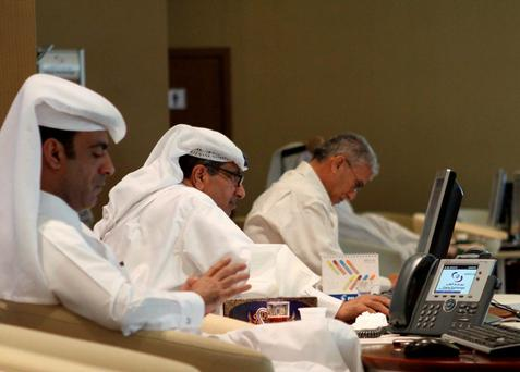 Traders look at share prices on their monitors at the Doha Stock Exchange in Doha, Qatar. Photo: Reuters