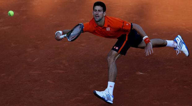 Novak Djokovic hits a return against Rafael Nadal at Roland Garros