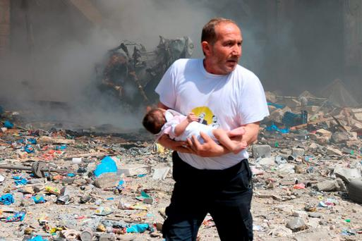A man holds a baby who survived what activists said was an explosion of a barrel bomb dropped by forces loyal to the Syrian President Bashar al-Assad at the old city of Aleppo yesterday. Photo: Reuters