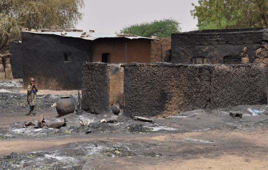 A child walks past burnt out houses following Sunday's attack by Boko Haram militants in Gubio, Nigeria, Tuesday, May 26, 2015. (AP Photo/Jossy Ola)