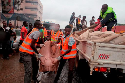 Rescue workers carry the remains, of a person onto the back of a truck after being killed in a gas station explosion in Accra, Ghana. Photo: AP