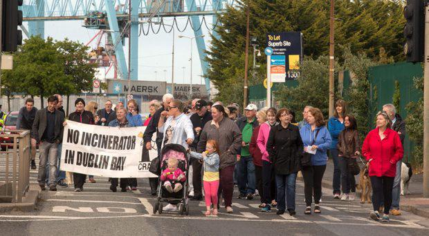 Residents march on the Sean Moore road to protest against the the incinerator been built in the area
