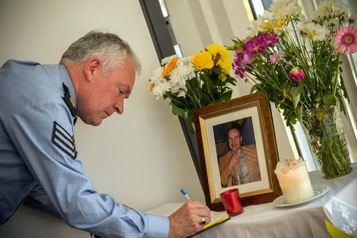 Sgt Iggy Larkin signs the book of condolences for Sgt Galvin at Ballyshannon Garda Station, in Co Donegal. Photo: James Connolly