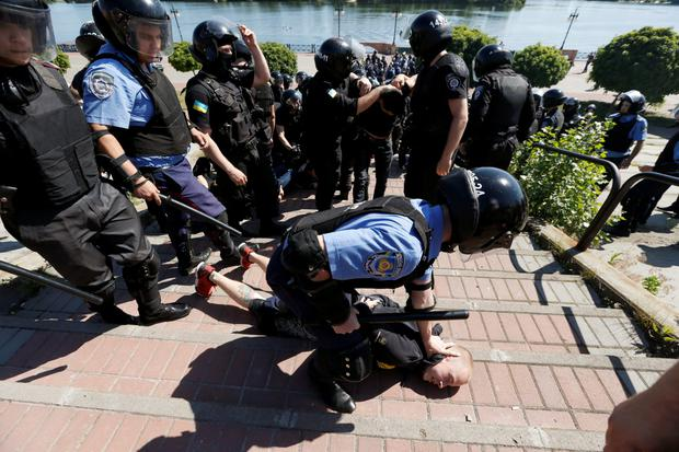 An Interior Ministry member detains an anti-gay protester during an 'Equality March' in Kiev Credit: REUTERS/Stringer