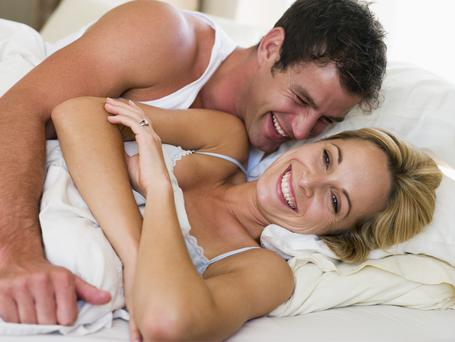 man and women awake in bed laughing
