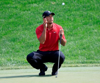 Tiger Woods prepares to catch his golf ball during his final round at the Memorial Tournament
