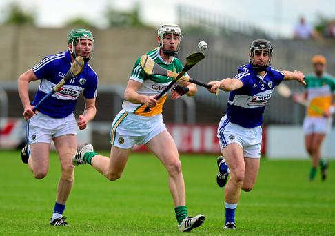 Emmet Nolan tries to keep possession under pressure from John Delaney and Zane Keenan