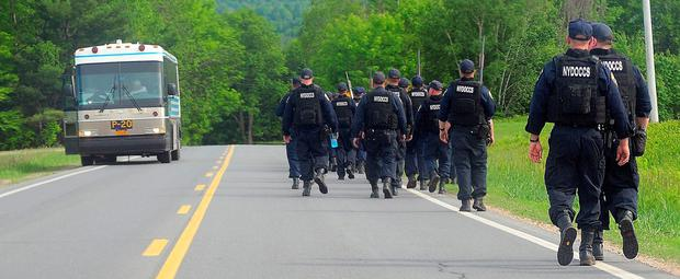 Law enforcement officers search for two escaped prisoners Sunday, June 7, 2015, near Dannemora, N.Y. (Rob Fountain/The Press-Republican via AP)