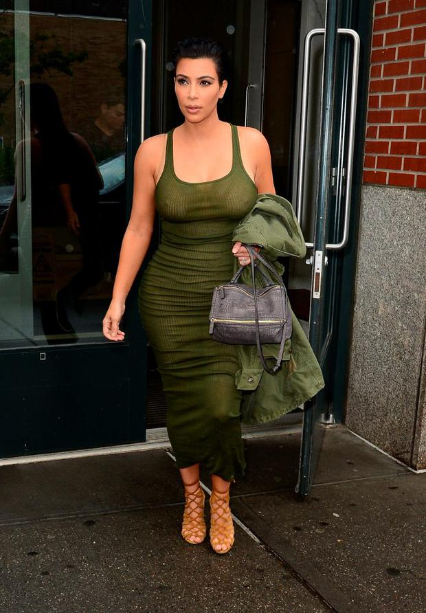 June 2, 2015: Her tiny baby bump is visible in an olive green midi dress as she leaves her New York City apartment.