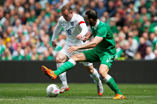 England's Wayne Rooney (L) in action with Ireland's Marc Wilson
