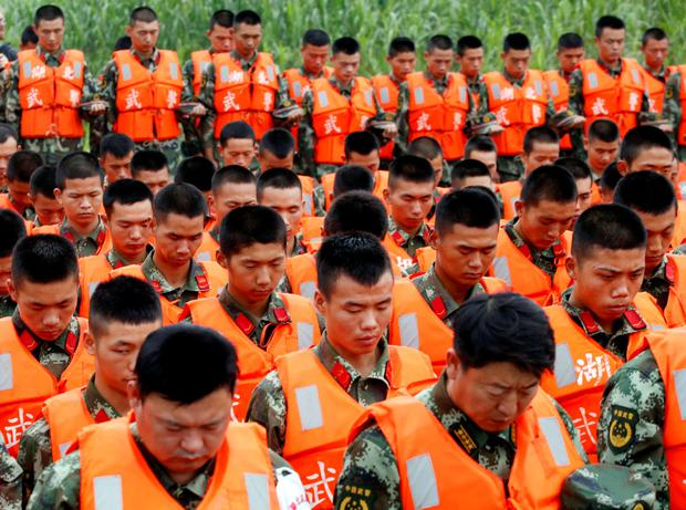 Paramilitary soldiers hold a moment of silence at a ceremony to mark seven days since the Eastern Star went down in the Jianli section of Yangtze River, Hubei province, China, June 7, 2015. REUTERS/Kim Kyung-Hoon