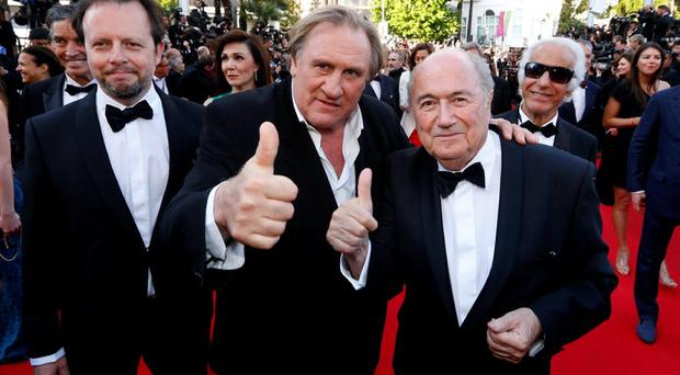 Actor Gerard Depardieu (C), FIFA President Sepp Blatter (R) and director Frederic Auburtin pose on the red carpet for the screening of the film