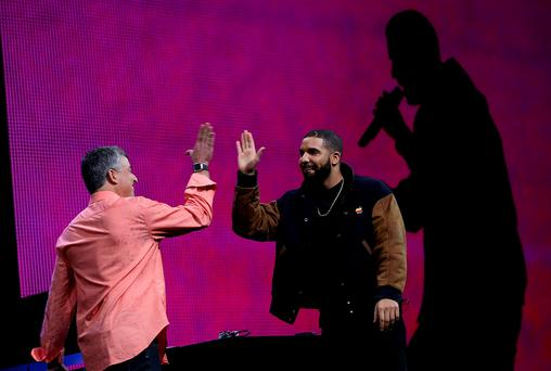 Apple executive Eddy Cue high-fives singer Drake during the Apple Music introduction at the Apple WWDC in San Francisco, California
