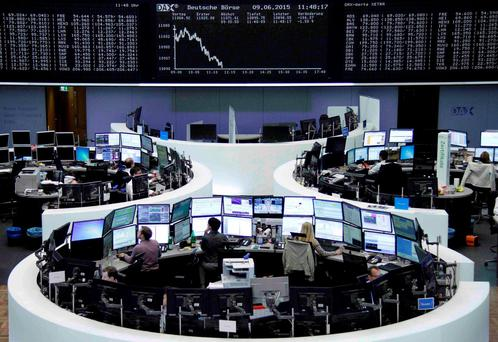 Traders work at their screens in front of the German share price index DAX board at the stock exchange in Frankfurt, Germany. Photo: Reuters
