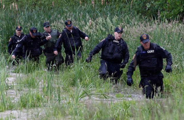 Law enforcement officers walk in water while searching a field near Willsboro, New York June 9, 2015. REUTERS/Chris Wattie