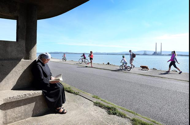Sr Anne reads a book on Dollymount Strand. Photo: Steve Humphreys