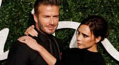 Former England football captain David Beckham and his wife British fashion designer and singer Victoria pose for pictures on the red carpet upon arrival to attend the British Fashion Awards 2014