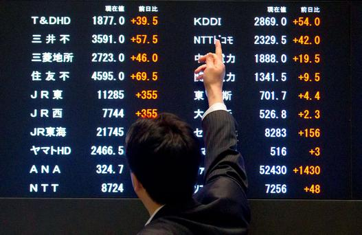 A man points at market indices at the Tokyo Stock Exchange (TSE) in Tokyo. Photo: Reuters