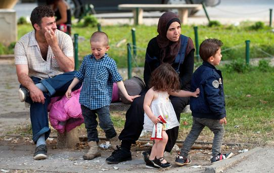 A family of migrants on their way to western Europe rest at a train station in Demir Kapija, Macedonia. Photo: AFP/Getty Images