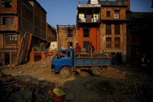People sit on a truck loaded with wood recovered from a house that collapsed during the April 25 earthquake in Bhaktapur, Nepal, June 5, 2015. REUTERS/Navesh Chitrakar