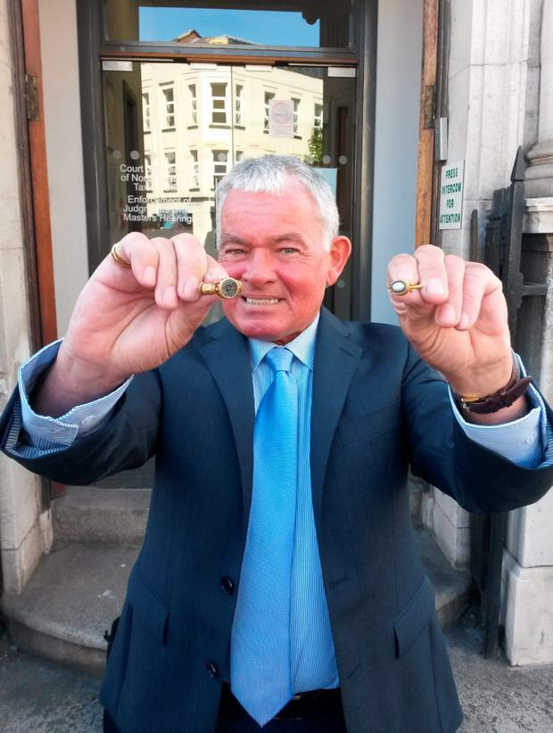 Retired civil servant Brian Murray holds two ornate Roman gold rings that he found on Murlough beach in Co Down outside a coroner's court in Belfast after they were officially declared as treasure. David Young/PA Wire