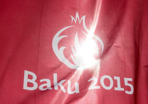The sun is pictured through a flag promoting the 2015 European Games at Bilgah Beach of the Caspian sea in Baku