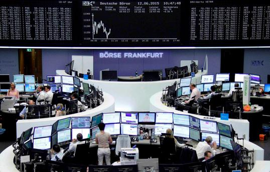 Traders are pictured at their desks in front of the DAX board at the stock exchange in Frankfurt, Germany. Photo: Reuters