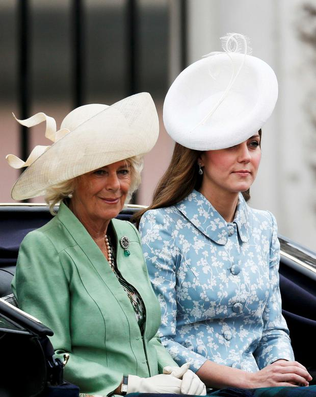 Britain's Catherine, the Duchess of Cambridge (R) and Camilla the Duchess of Cornwall and Prince Harry leave Buckingham Palace by carriage to attend the Trooping the Colour ceremony